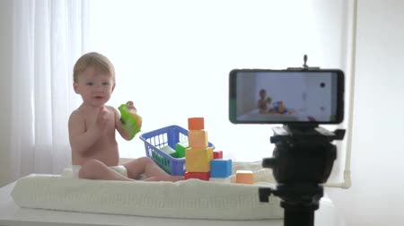 relieves : blogging, happy smiling baby boy is playing with toys and clapping hands while writing online streaming live on smartphone for followers in social networks in bright room Stock Footage