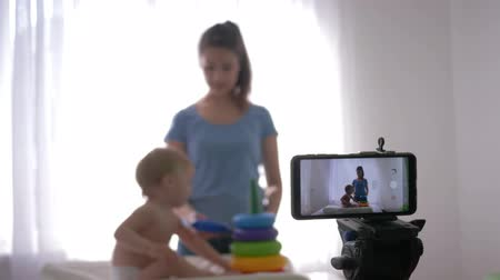 subscribers : blog upbringing child, young mother blogger with child plays developing toys while recording live tutorial video on smartphone for subscribers on social networks at home