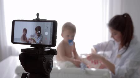 relieves : blogging, pediatrician woman with stethoscope professionally examines little patient boy during recording live tutorial video in streaming live on mobile phone for subscribers at clinic Stock Footage