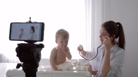 relieves : online studying,doctor woman with stethoscope checks to heartbeat and breath of crying kid boy during recording education video in live broadcast on smartphone for followers at clinic