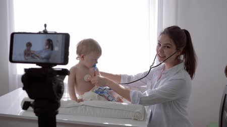 relieves : videoblog, medic female with stethoscope listens to heartbeat and breath of patient infant boy during recording training video in streaming live on cell phone for subscribers at hospital