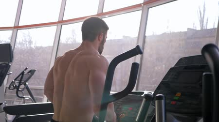 apparatus : cardio workout, attractive bodybuilder with big muscles running on treadmill at sports center in natural light against window