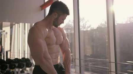 naga : professional bodybuilding, sports male keeps muscles in tension and looks at result of strength training at sports center near window in sunlight