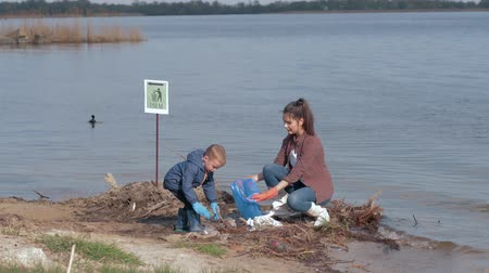 nurture : care nature ecology, little child boy helps female volunteer activist clean up polluted river shore from plastic trash and collected in garbage bag saving environmental