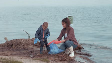 nutrir : ecological care, young mum with child boy volunteers clean polluted nature from plastic garbage near water on river waterfront
