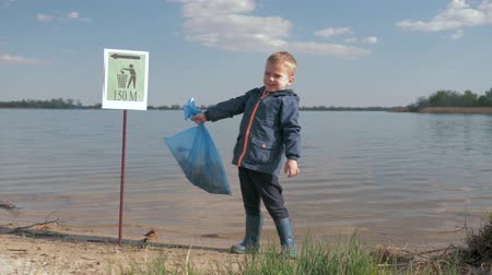 nurture : ecological pollution refuse in nature, portrait of kid boy with garbage bag in hand after cleaning up plastic rubbish and domestic waste on river quayside Stock Footage