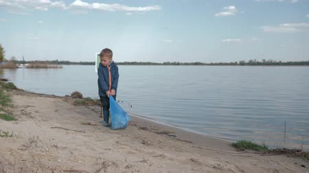 nutrir : ecological purification of nature, little child boy pulls heavy bag of trash on pointing sign on river beach after cleaning up plastic garbage and domestic waste Stock Footage