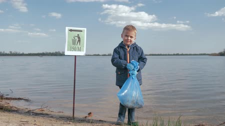 nutrir : environmental problem pollution rubbish, portrait of little child boy with garbage bag in hand after cleaning up plastic trash and domestic waste on river embankment