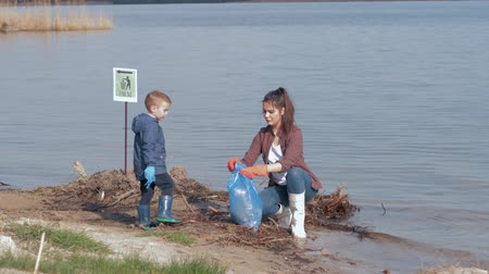 nutrir : environmental problems solutions, little boy helps woman volunteer activist clean up dirty river waterfront from plastic trash and collected in garbage bag saving ecology nature