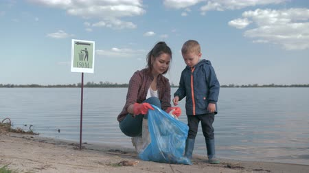 nutrir : environmental volunteers, young woman is consider with kid boy how much rubbish is collected in garbage bag while cleaning beach from plastic trash and give thumb up near river embankment Stock Footage