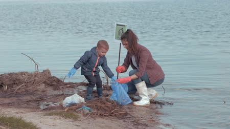 nurture : family cleaning beaches, young female volunteers with kid boy clean polluted nature from plastic trash near water on embankment river Stock Footage