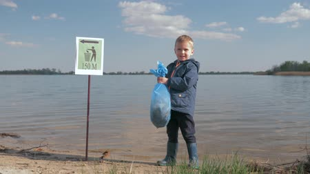 nutrir : problem ecological pollution litter in nature, portrait of little boy with garbage bag in hand after cleaning up plastic refuse and domestic waste on river waterfront