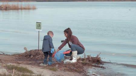 nutrir : save planet, young mother with little son volunteers clean polluted beach from plastic trash near water on river embankment