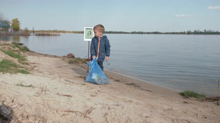 nutrir : stop pollution, little cute boy pulls heavy bag of trash on pointing sign on river beach after cleaning up plastic garbage and domestic waste