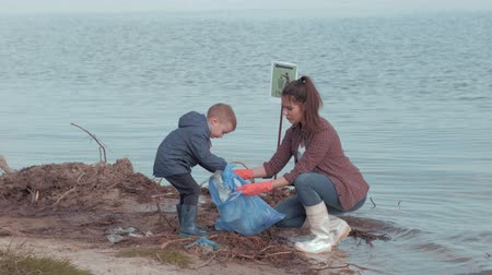 nutrir : stop pollution, young woman volunteers with little child boy clean dirty coast from plastic trash on river waterfront Stock Footage
