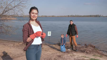 nutrir : young society against pollution, Portrait of smiling woman volunteer gives thumb up on unfocused background of family with small child while cleaning dirty beach from plastic trash Stock Footage