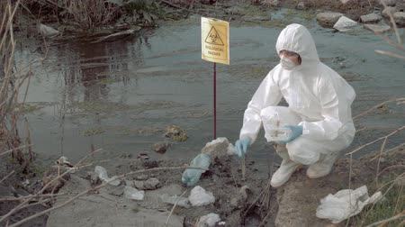 peril : Biohazard Emergency in nature, hazmat worker into uniform and mask taking infected water sample in test tubes for testing in contaminated lake with pointer sign biological hazard Stock Footage