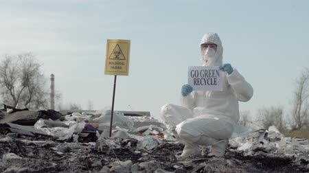 enviroment : Biohazard Emergency, Hazmat biologist into Protective Costume and mask shows sign go green recycle on rubbish dump with pointer biological hazard Stock Footage