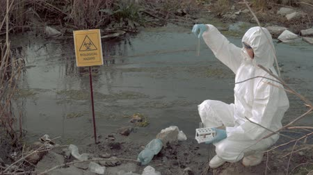peril : bio-hazard in nature, hazmat chemist into protective suit and mask taking infected water sample in test tubes for testing in contaminated river with pointer sign biological hazard Stock Footage