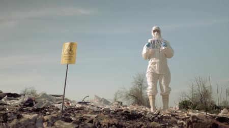 wijzer : bio-hazard, Hazmat scientists into Protective Coveralls and mask shows sign think green on landfill with pointer biological hazard on open air