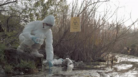 peril : biological danger in nature, hazmat researcher into Protective Costume and mask taking infected water sample in test tubes for testing in contaminated lough with pointer sign bi