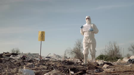 peril : biological danger, Hazmat man into Protective clothing and mask shows sign save the planet on rubbish dump with pointer biological hazard Outdoors