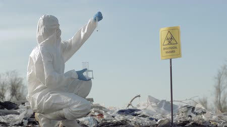 peril : biological hazard, Hazmat chemist into protective clothing and mask taking infected garbage sample in test tube for examining on landfill with pointer sign biological hazard Stock Footage