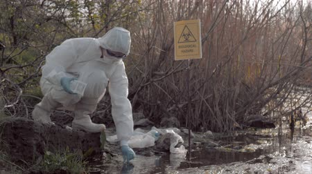 enviroment : Dangerous job, hazmat biologist into protective clothing and mask taking infected water sample in test tubes for examining in contaminated loch with pointer sign biological hazard