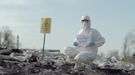 peril : Enviroment pollution, Hazmat man into uniform and mask shows sign save the planet on landfill with pointer biological hazard Stock Footage