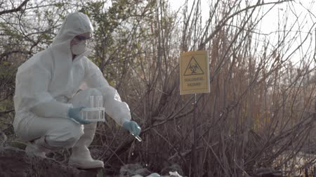 hazmat : Environmental pollution problem in nature, hazmat into Protective Coveralls and mask taking infected water sample in test tubes for examining in contaminated loch with pointer sign bi