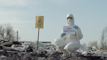 peril : Environmental pollution problem, Hazmat Worker into protective clothing and mask shows sign stop pollution on rubbish dump with pointer biological hazard
