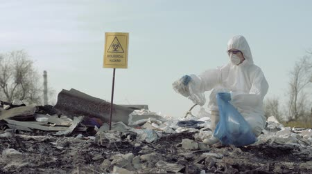 peril : environmental pollution, Hazmat investigator into protective suit and mask collects litter in garbage bag for Research on rubbish dump with pointer sign biological hazard