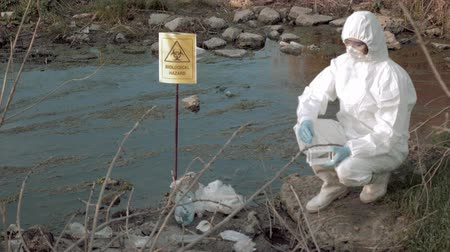peril : exclusion zone in nature, hazmat virologist into Protective clothing and mask taking infected water sample in test tubes for research in contaminated lake with pointer sign biological hazard Stock Footage