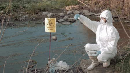 peril : hazardous area research, hazmat scientists into protective clothing and mask taking infected water sample in test tubes for examining in contaminated river with pointer sign biological hazard Stock Footage