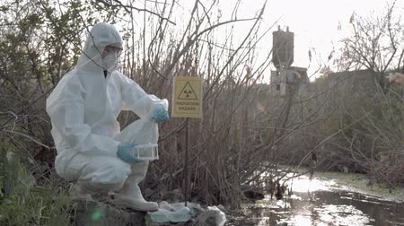 peril : hazardous area, Hazmat into Protective Coveralls and mask taking infected water sample for examining in contaminated loch with pointer sign radiation hazard Stock Footage