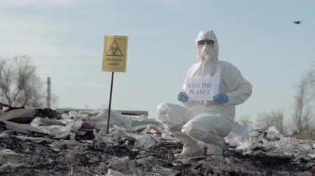 hazmat : hazardous area, Hazmat scientist into protective suit and mask shows sign save the planet on junk yard with pointer biological hazard
