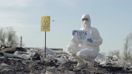 peril : Hazmat biologist into Protective suit and mask shows sign think green on junk yard with pointer radiation hazard on open air Stock Footage