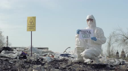 peril : Hazmat person into Protective Costume and mask shows sign think green on rubbish dump with pointer radiation hazard Outdoors