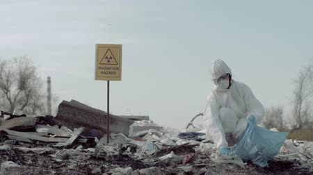 wijzer : radiation contamination, Hazmat scientist into protective clothing and mask collects trash in garbage bag for examining on junk yard with pointer sign radiation hazard
