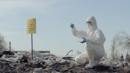 çöplük : radiation hazard, Hazmat virologist into uniform and mask taking infected trash sample in test tube for examining on rubbish dump with pointer sign radiation hazard Stok Video