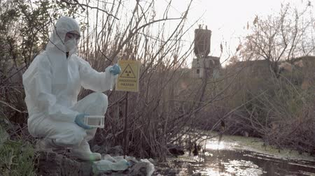 peril : radioactive zone, Hazmat chemist into Protective Costume and mask taking infected water sample for testing in contaminated lake with pointer sign radiation hazard