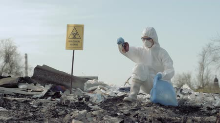 wijzer : save planet save planet from trash, Hazmat researcher into protective uniform and mask collects refuse in garbage bag for testing on landfill with pointer sign biological hazard Stockvideo