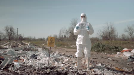 szlogen : biological hazard, young woman in uniform and protective glasses holding poster think green standing at a trash dump in rubber boots near sign