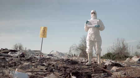 szlogen : ecological disaster, woman in protective suit and mask holding poster with stop pollution slogan at landfill near a sign biological hazard