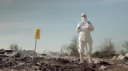 szlogen : environmental movement, girl in mask and protective costume holding poster with stop pollution slogan at trash dump with sign biological hazard