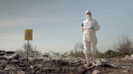 лозунг : environmentalism, woman in protective costume and mask holding poster with stop pollution slogan at landfill site with garbage near a sign biological hazard Стоковые видеозаписи