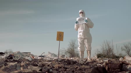 szlogen : wastes of human life, woman in uniform and protective glasses holding poster think green standing at landfill in rubber boots on background of sky with birds