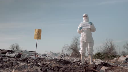 szlogen : woman in protective suit and mask holding poster with stop pollution slogan at garbage dump near a sign biological hazard