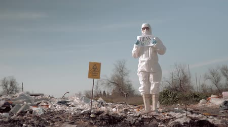 szlogen : young woman in uniform and protective glasses holding poster think green standing at a garbage dump in rubber boots near sign biological hazard Stock mozgókép