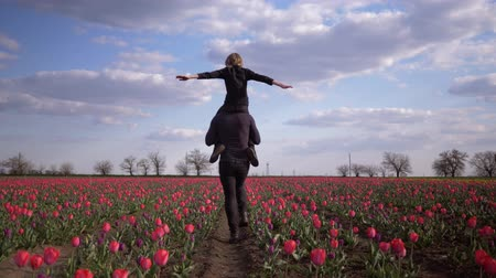 小花 : children-parents relationship, daddy with adolescent boy spread arms to side sitting on shoulders having fun on blossom field of tulips against sky